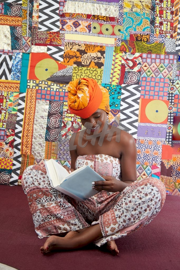 Gorgeous lady in jumpsuit and head wrap sits with her legs crossed on a maroon carpet reading a book