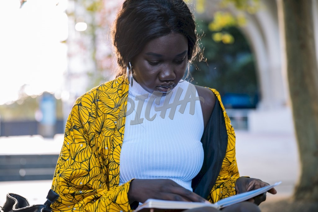 Young lady in yellow and white reads a book outside