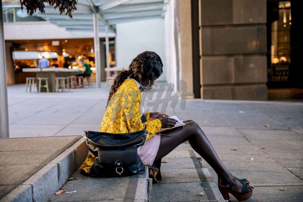 stylish young lady sits out on the pavement