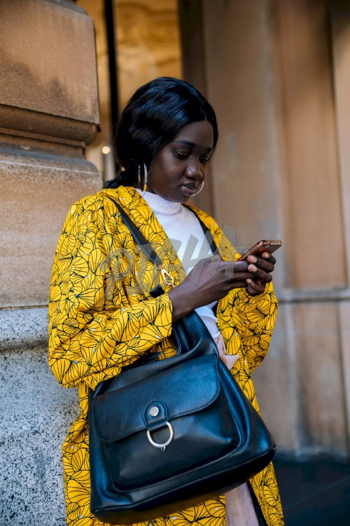 young lady in yellow kimono looks down at her cell phone