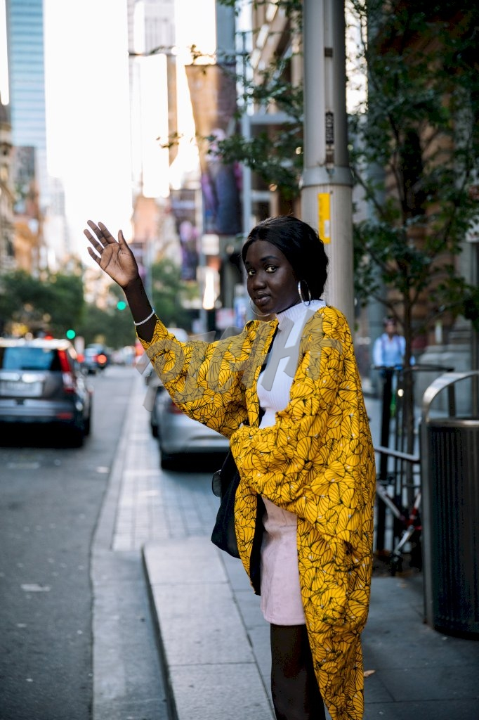 young lady in stylish yellow kimono flags a taxi