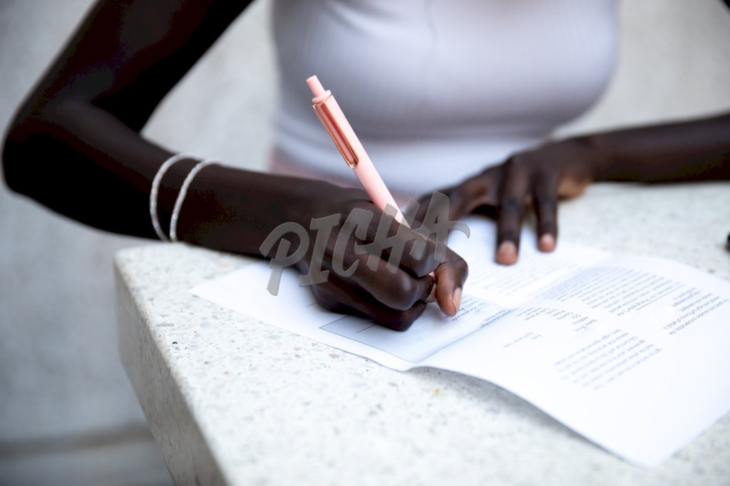 Young lady in white top taking notes