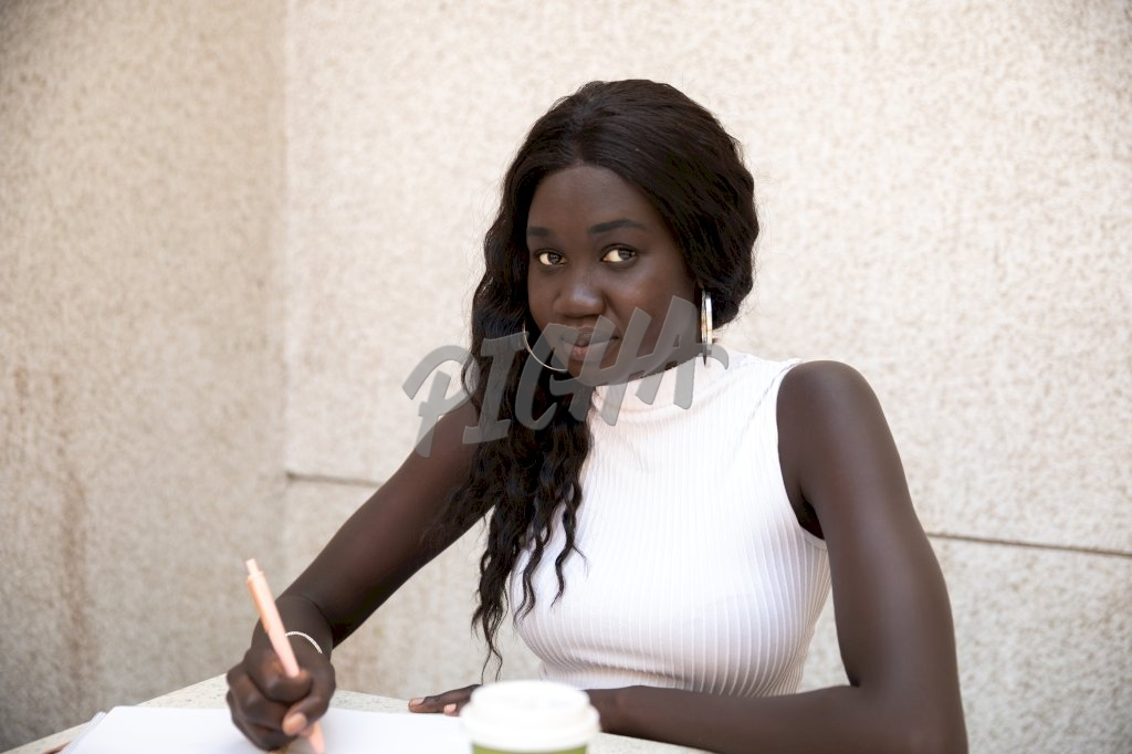 Young stylish lady in a white sleeveless turtleneck at her desk