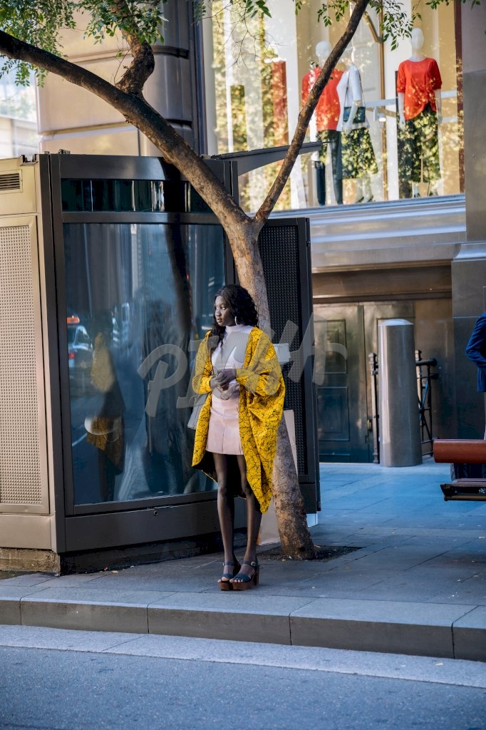 Stylish young lady in yellow kimono standing out in the street