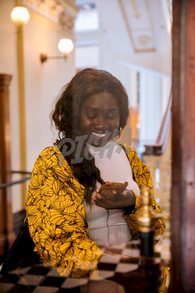 Young lady smiles down at her phone