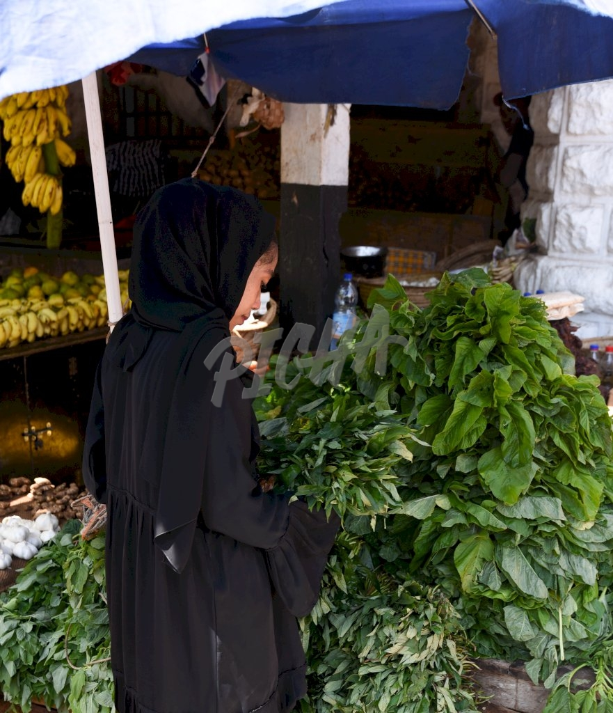 woman in burka shopping for herbs