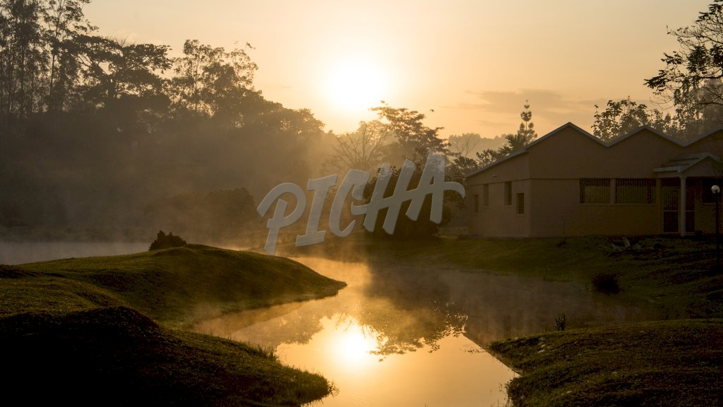 sunrise eclipses a bungalow by the river