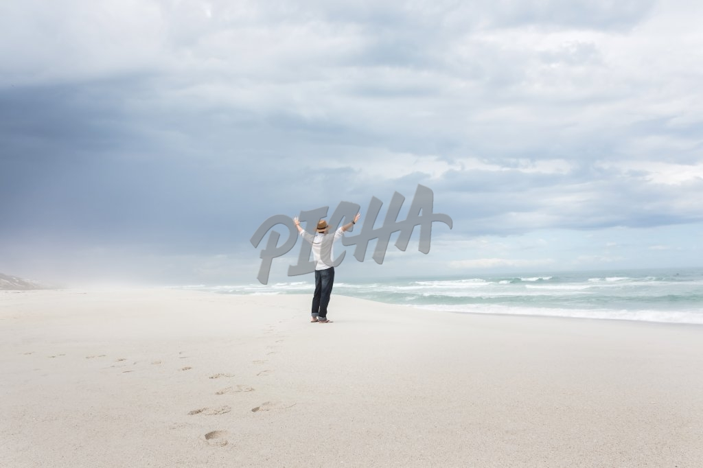 Back view of a young man at the beach wearing a sunhat and smart casual clothes with hands in the air celebrating freedom.