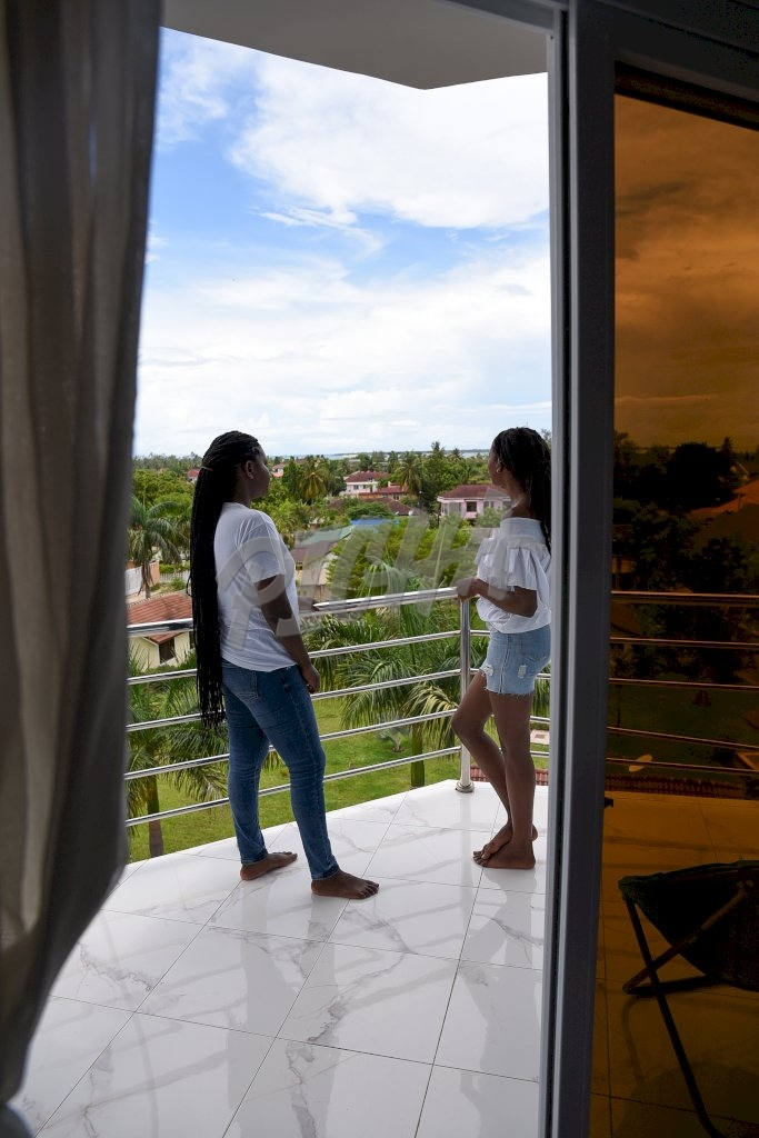 ladies chat while standing on balcony