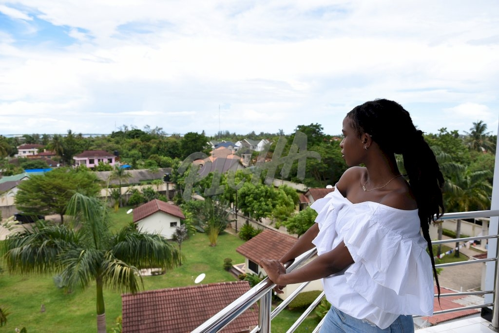 woman in white off shoulder top standing on balcony