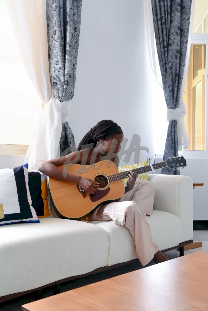 woman plays the guitar while seated on couch