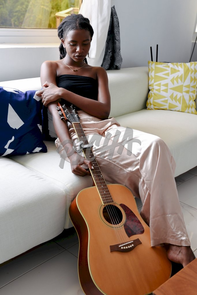 Woman poses with a guitar