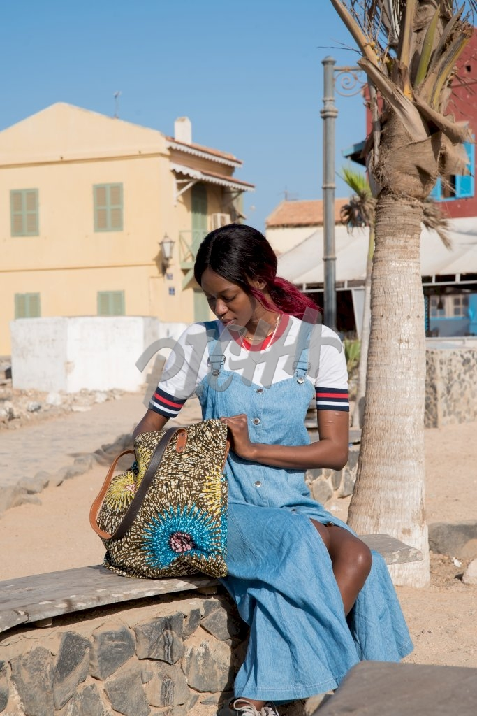 lady in blue dungaree dress looks through her bag while seated on outdoor stone bench