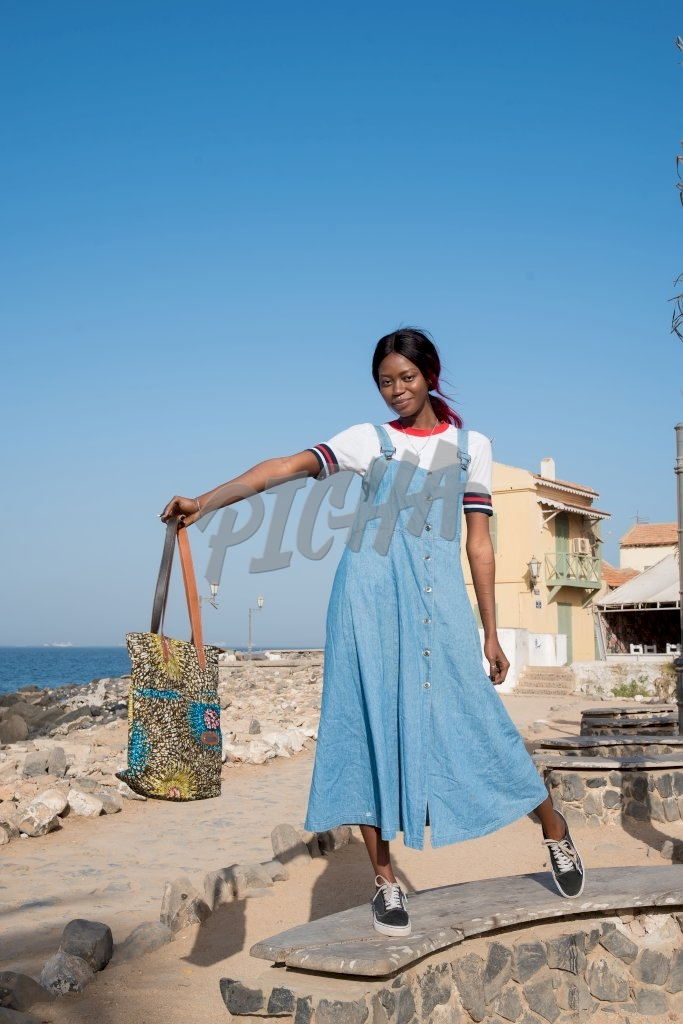 lady in long blue dungaree dress stands on bench with tote bag in hand