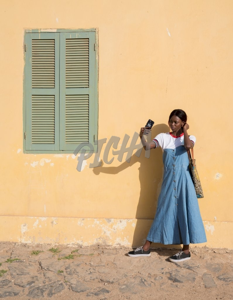 lady takes a selfie by a peach wall in the street