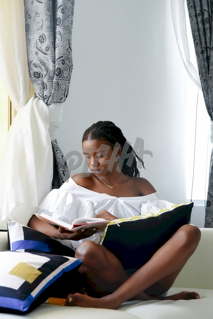 lady reads book while seated with legs crossed on white couch