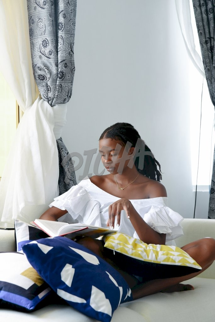 lady reads a book while seated on couch