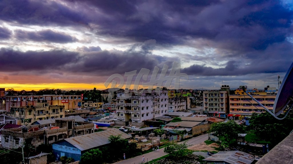 Rooftop view overlooking several flats covered by stirring clouds