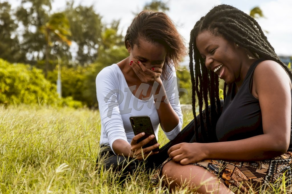 Ladies sitting on grass using a phone