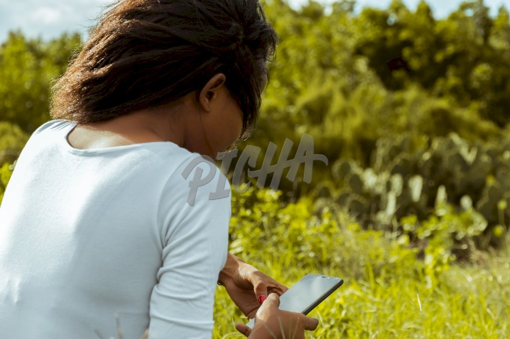 lady uses her phone with both hands outdoors