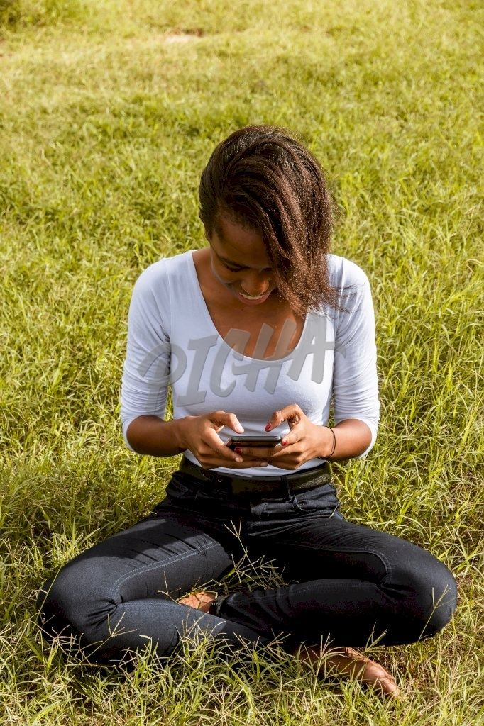 lady uses her phone with both hands while seated on the grass