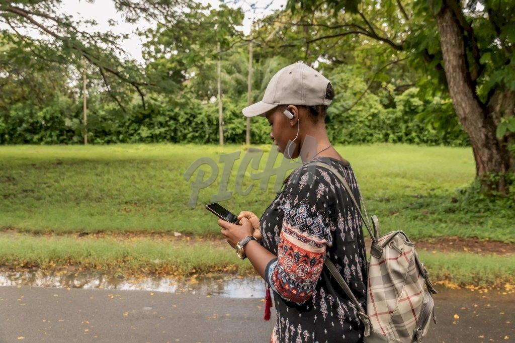 girl with bag and cap walks while chatting and listening to music
