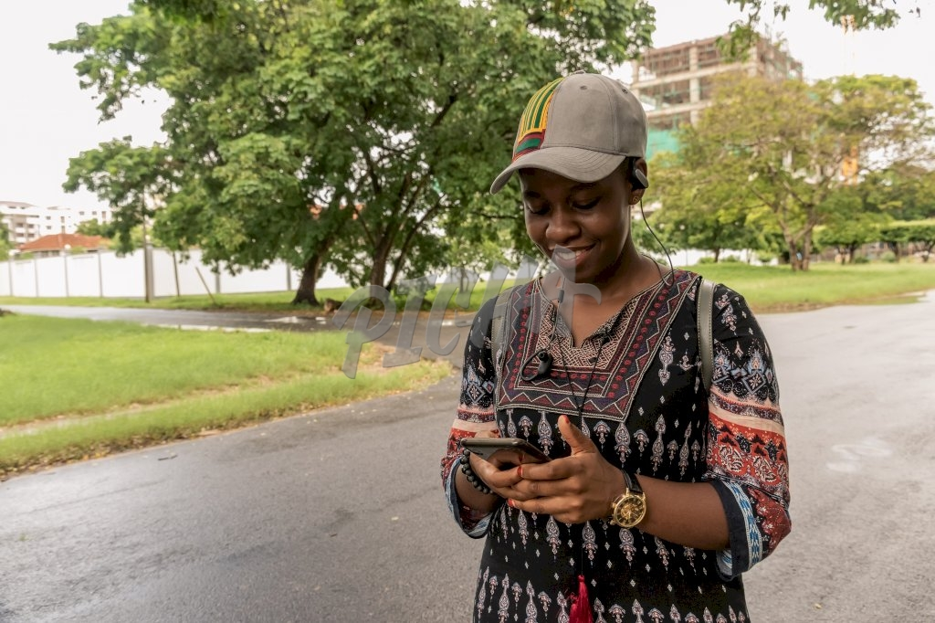 lady smiles as she uses her phone to chat and listen to music