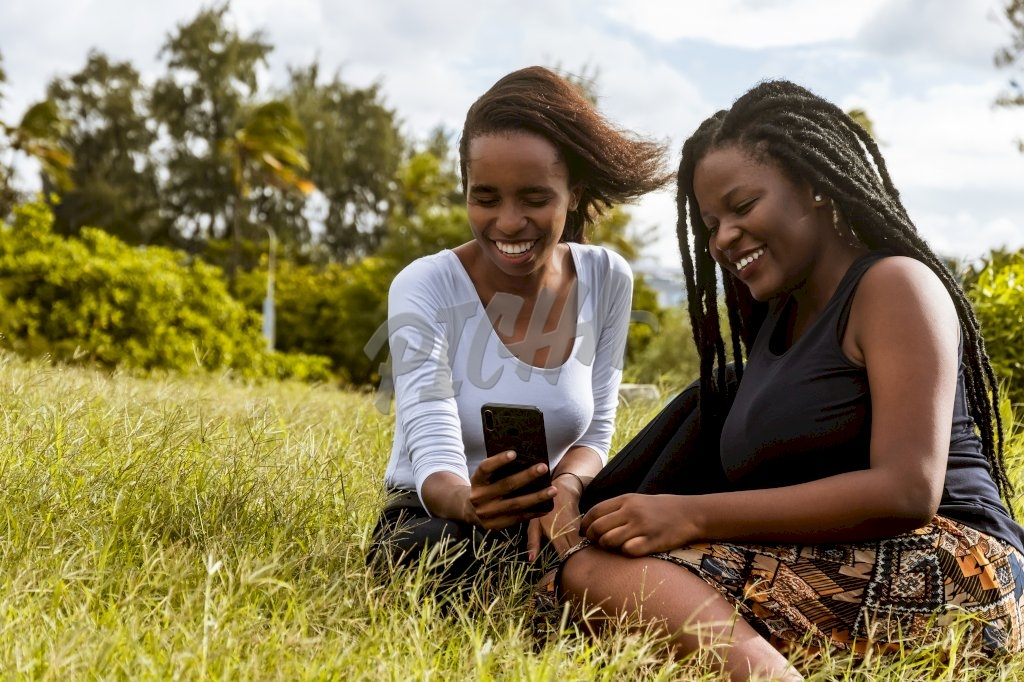 Two ladies sitting on the grass using a phone