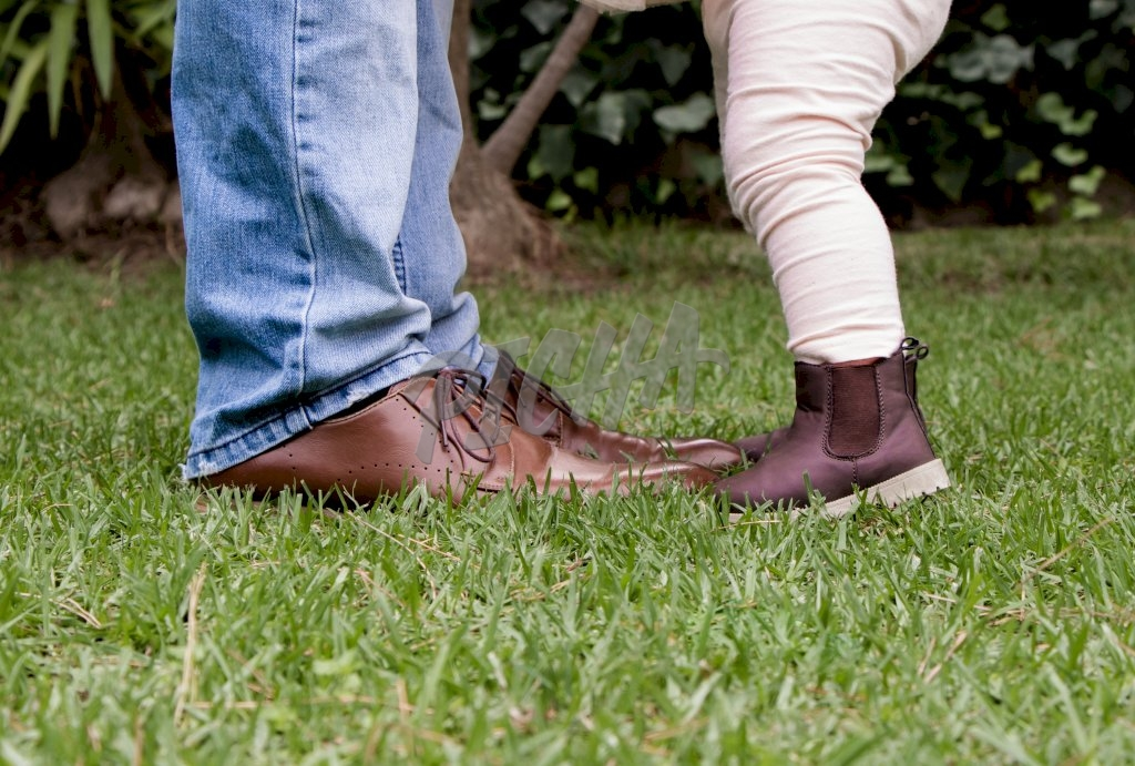 legs of father and child as they stand in the grass