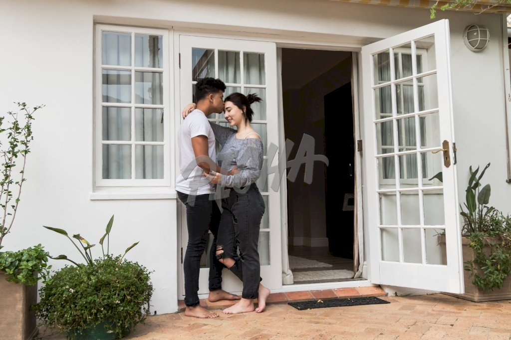 man kisses his girlfriend on the forehead outside doorway