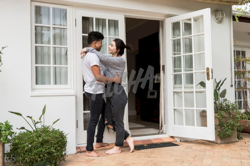 couple has an intimate conversation outside their doorway