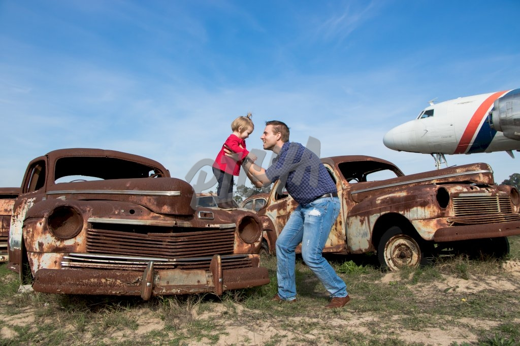 Father hoists his daughter onto a rusty car hood for fun