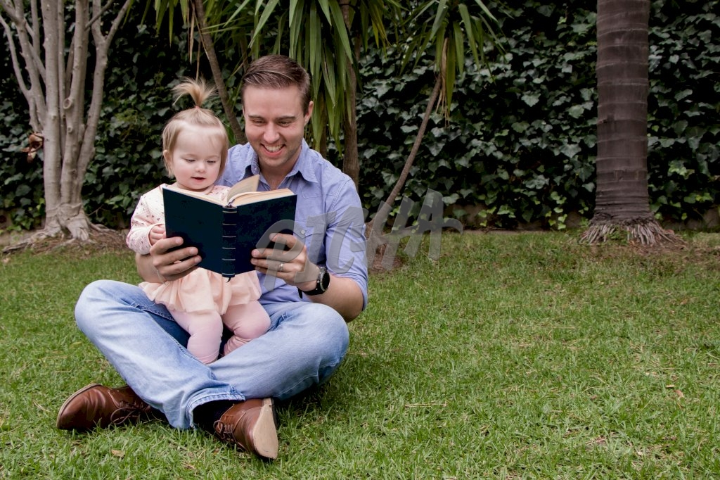 father reads a story to his daughter while seated out on the grass