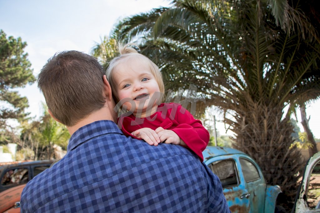Child looks back gleefully while carried by father