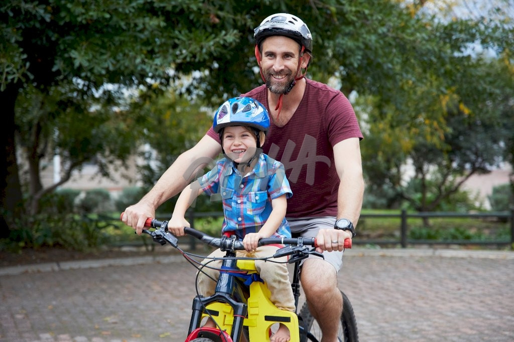 Father lets son ride along on his bike while using a ride along assist accessory