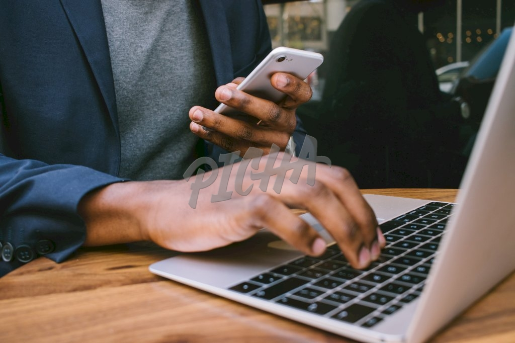 man takes a moment to use his phone while working