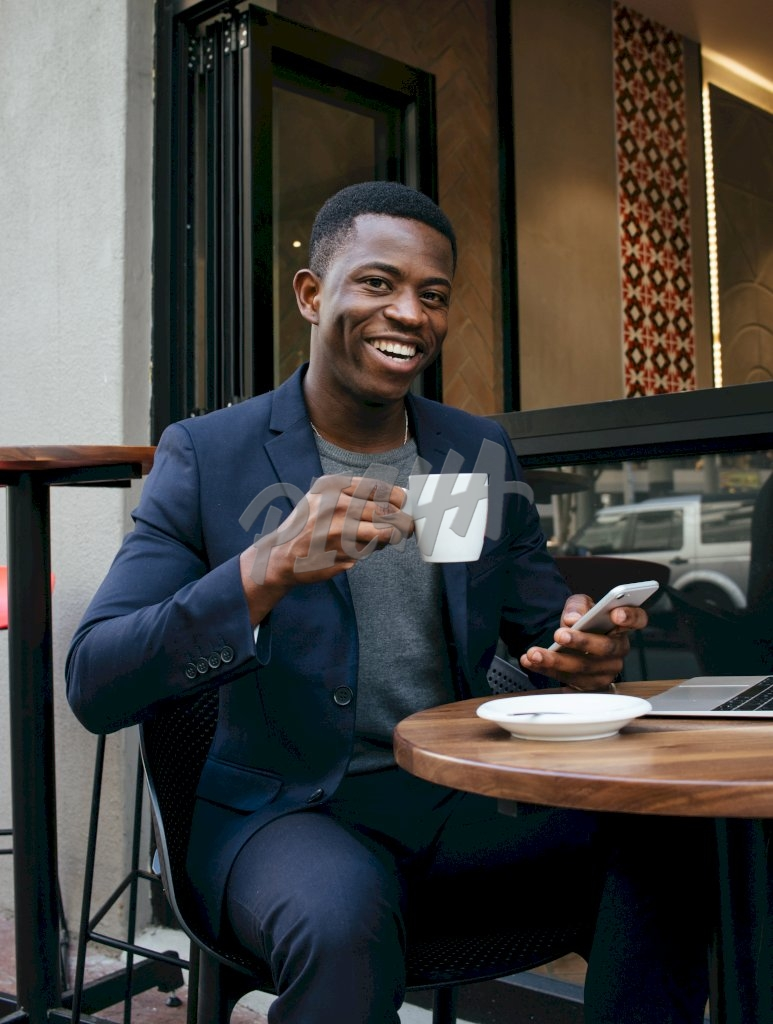 smart man looks up from his phone with a smile while at a coffee shop