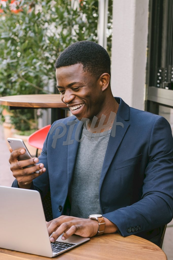 smartly dressed man smiles broadly after looking at his phone