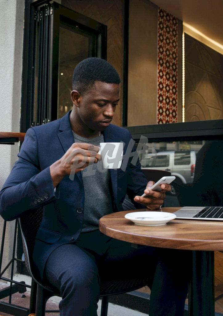 smart man pauses from his coffee to take a look at his phone