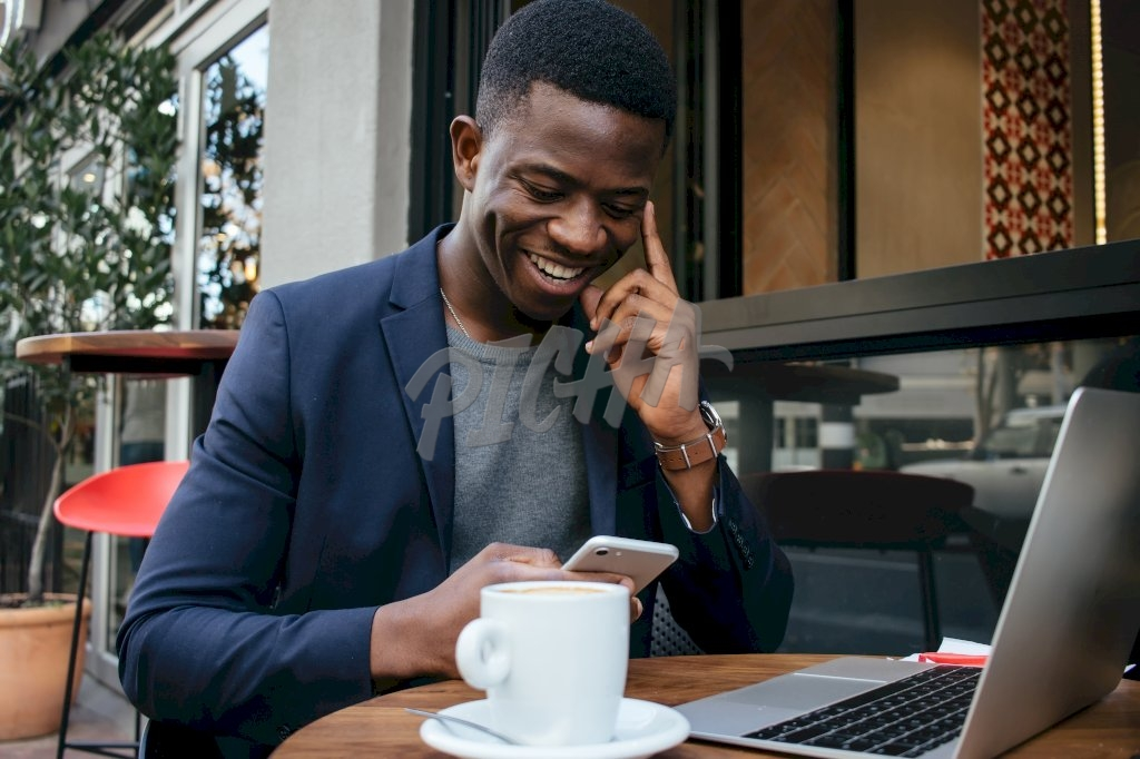 man smiles as he looks through his phone at a coffee shop