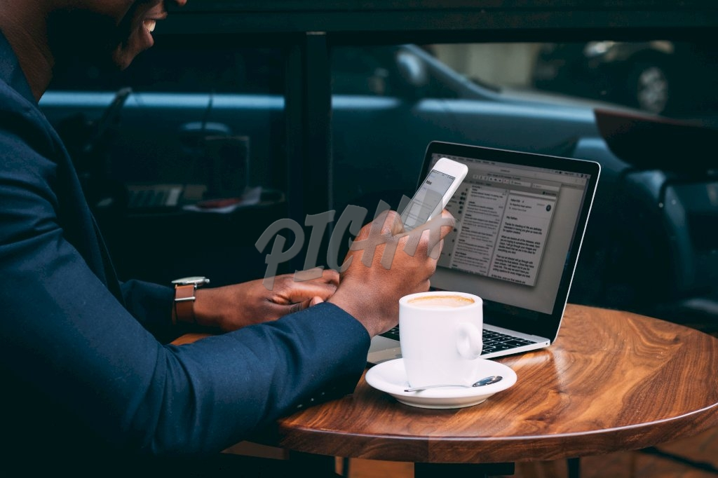 man smiles as he uses his phone while working at a coffee shop