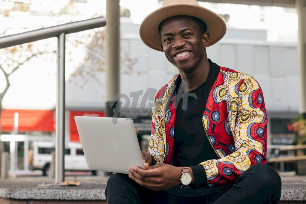 stylish man smiles as he looks up from his computer