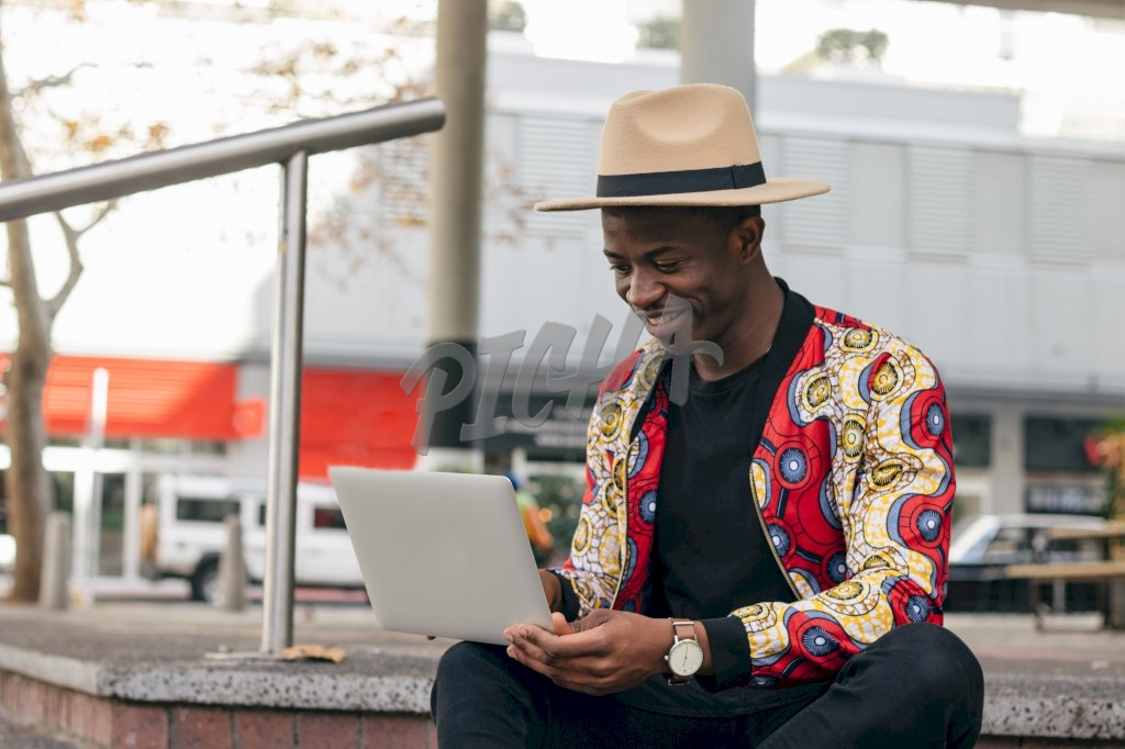 stylish man uses his laptop while seated out in the street
