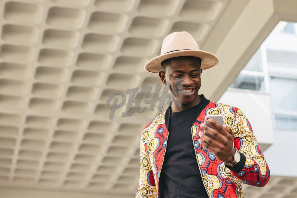 Man in a hat checking his phone