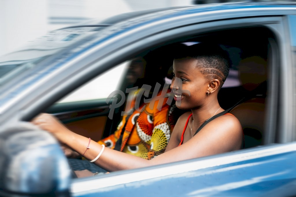 young lady drives past in a blue saloon vehicle