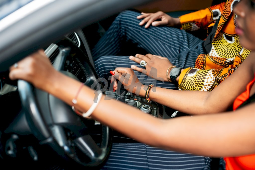 lady steers a car with one hand while resting the other on the gear stick