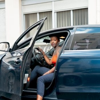 driver casually puts her foot outside the saloon car door