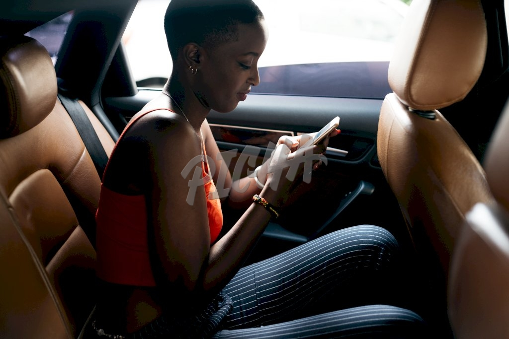 lady is preoccupied by her phone while in the backseat of a car