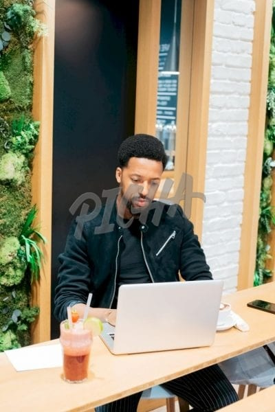 man in black jacket works on his laptop while at a cafe