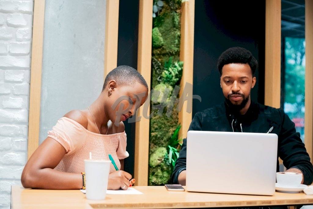 Young man works on his laptop while a lady takes notes on a notepad